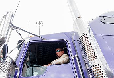 Man driving semi-truck - p1427m2066681 by Jamie Grill