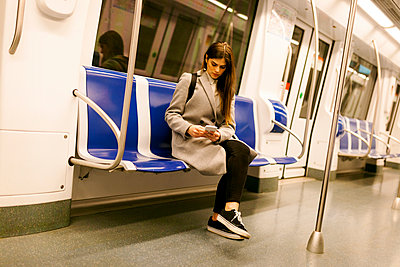 Spain, Barcelona, woman sitting in underground train using cell phone - p300m1587922 von Valentina Barreto