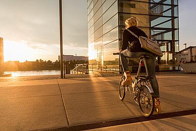 Senior woman with city bike at the riverside at sunset - p300m2004598 von Jo Kirchherr