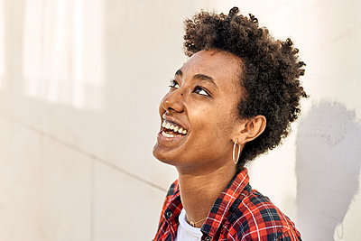 Smiling young Afro female hipster looking up against white wall - p300m2241783 by Veam