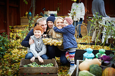 Portrait of happy family with fresh produce in back yard - p426m2169037 by Maskot