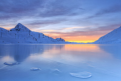The colors of dawn invading the smooth surface of Lago Bianco exceptionally icy, Bernina Pass, Graubunden, Swiss Alps, Switzerland, Europe - p871m1011660f by Roberto Moiola