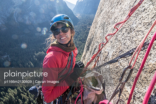 A young woman smiles while at a hanging belay on Washington Column - p1166m2130609 by Cavan Images