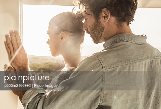 Affectionate young couple at the window at sunset - p300m2166992 by Floco Images
