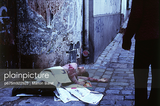 Woman lying under newspapers in alley, silhouetted figure watching in foreground - p675m922923 by Marion Barat