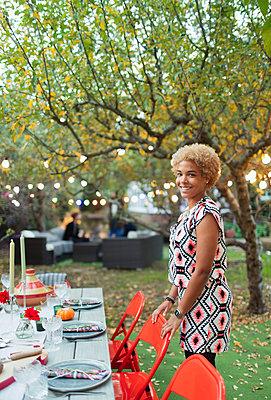 Portrait happy woman hosting dinner garden party - p1023m2087968 by Paul Bradbury