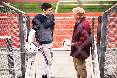 High angle view of coach discussing with American football player at stadium - p1166m1423132 by Cavan Images
