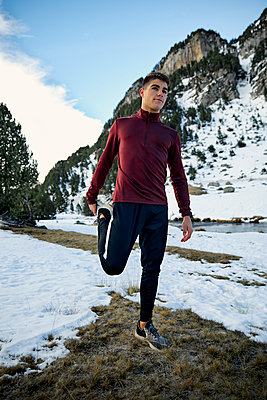 Young male athlete stretching while standing outdoors against sky during winter - p300m2250039 by Aitor Carrera Porté