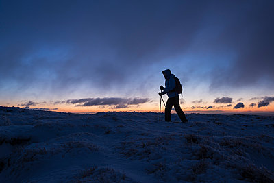 Silhouette of hiker on wintry summit of Corn Du at dawn - p343m896553f by Cody Duncan