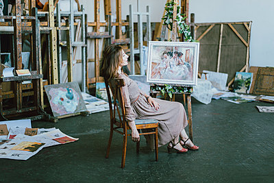 Caucasian artist sitting near painting on easel - p555m1523121 by Kateryna Soroka