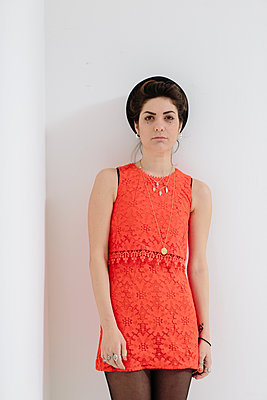 Female model in an orange dress against a white background. - p686m1124873 by Paul Tait