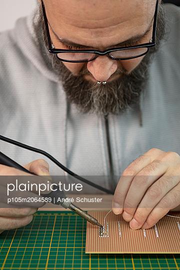 Elektriker lötet Bauteile auf eine Platine - p105m2064589 von André Schuster