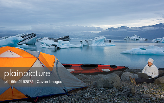 woman using her laptop at campsite by glacier lagoon - p1166m2182875 by Cavan Images