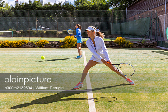 Mature women during a tennis match on grass court - p300m2132594 by William Perugini