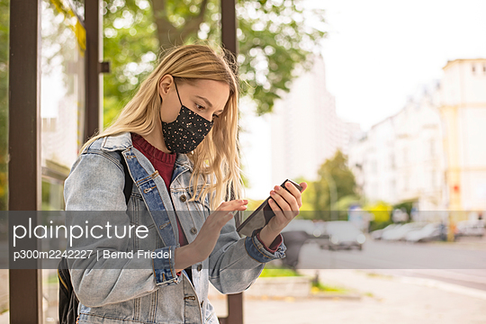 Woman using mobile phone at bus stop in city during COVID-19 - p300m2242227 by Bernd Friedel