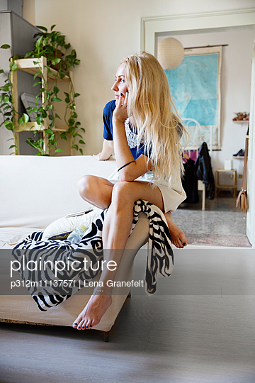 Young woman sitting on sofa in living room - p312m1113757f by Lena Granefelt