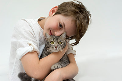 Boy huddling up to tabby cat - p267m1486975 by Ingo Kukatz
