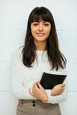 Portrait of smiling young woman with notebook at brick wall - p300m1587613 von Bonninstudio