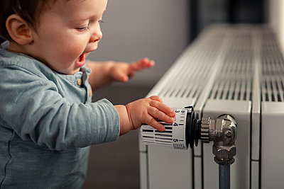 Excited baby boy playing with thermostat of heater - p300m2084073 by Sebastian Dorn