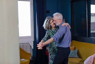 Senior couple dancing while standing at home - p300m2266030 by Emma Innocenti