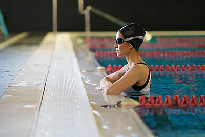 Female athlete looking away while leaning at poolside in water - p300m2286219 by Javier Sánchez Mingorance