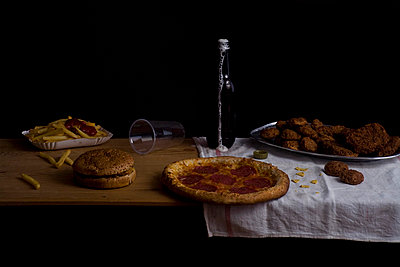 Variety of fast food and beer bottle, still life - p3018763f by Andreas Schlegel