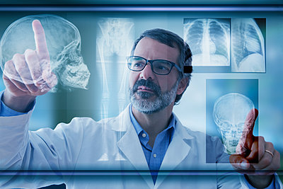 Hispanic doctor examining x-rays on virtual screen - p555m1232012 by REB Images