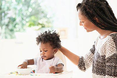 Black woman watching baby daughter eat cereal in high chair - p555m1305406 by JGI/Tom Grill
