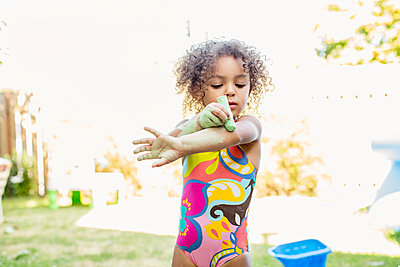 Mixed race girl putting chalk on her arm - p555m1479132 by Inti St Clair photography