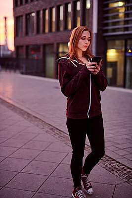 Young woman writing a text message - p890m2172105 by Mielek