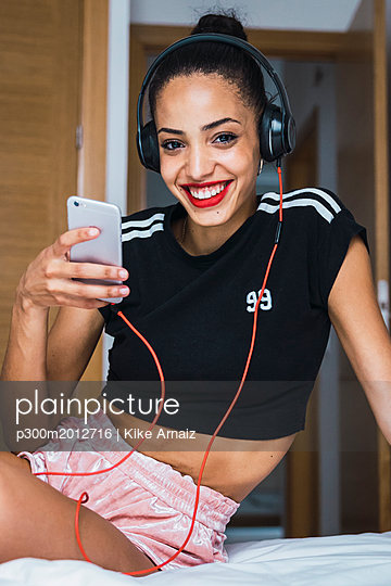 Portrait of smiling beautiful young woman sitting on bed with cell phone and headphones - p300m2012716 von Kike Arnaiz