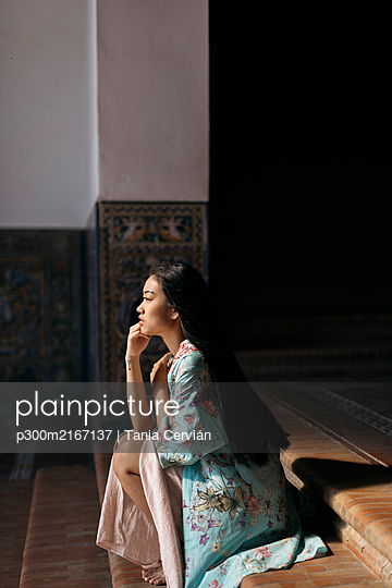 Portait of beautiful young woman sitting on steps wearing a kimono - p300m2167137 by Tania Cervián