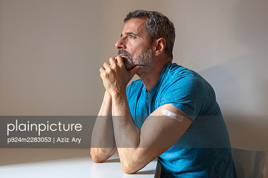 France, Man with bandage on arm sitting at table - p924m2283053 by Aziz Ary