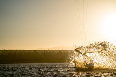 Young male athlete kiteboarding at sunset in La Ventana, Baja California, Mexico - p1166m2157126 by Cavan Images