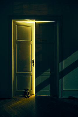 Apartment door at night with teddy bear on floor - p1312m2168094 by Axel Killian