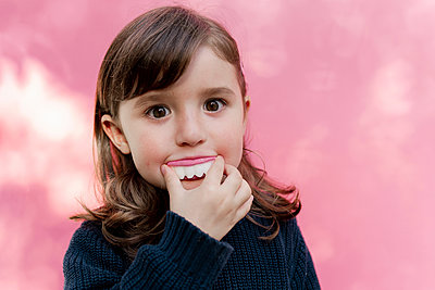 Portrait of little girl with false candy teeth in front of  pink background - p300m2170867 by Gemma Ferrando