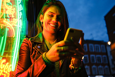 Smiling woman using mobile phone standing by illuminated light - p300m2273673 by Angel Santana Garcia