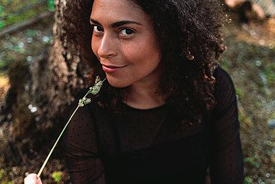 Smiling woman holding plant stem - p300m2281774 by Francesco Morandini