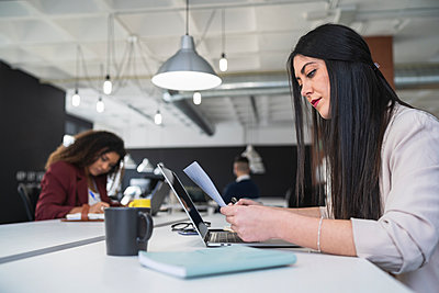 Businesswoman reading document with female colleague working in background at coworking office - p300m2282501 by SERGIO NIEVAS