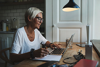 Mature female designer working late at home office - p426m1114712f by Maskot
