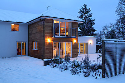 Illuminated family home in snow - p924m806961f by Simon Battensby
