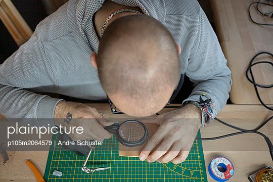 Sichtprüfung einer Platine mit Lupe - p105m2064579 von André Schuster