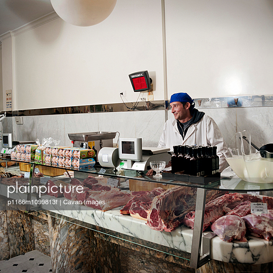 Smiling butcher standing at display cabinet in butcher shop - p1166m1099813f by Cavan Images