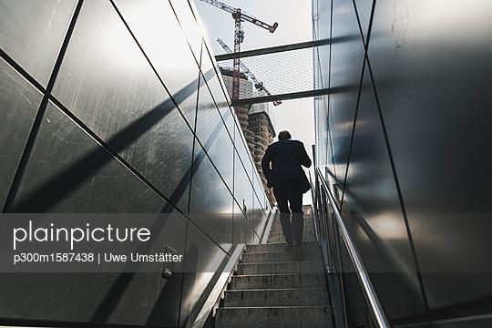 Businessman walking on staircase in the city - p300m1587438 von Uwe Umstätter