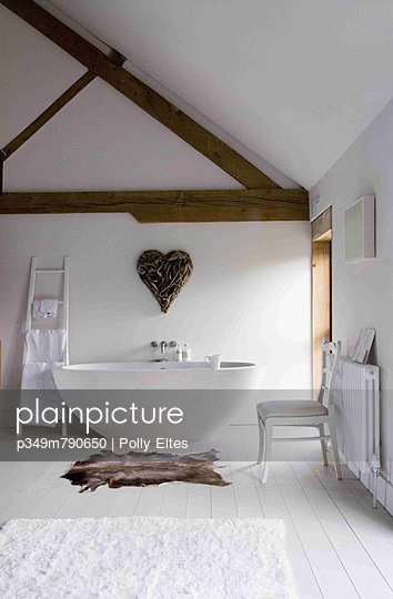 White bathroom with painted floorboards and free standing white bath - p349m790650 by Polly Eltes