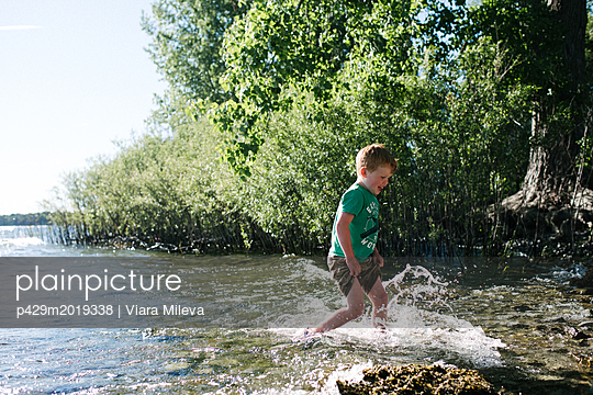 Boy running in water, Kingston, Canada - p429m2019338 by Viara Mileva