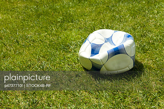 Flat soccer ball in grass, Germany