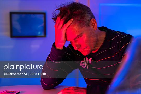 Man resting head on hand - p608m2258773 by Jens Nieth