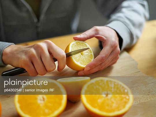 Frau schneidet Zitrone  - p6430254f von senior images RF