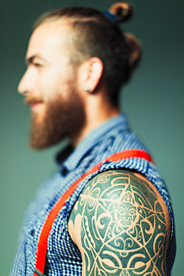 Close up hipster man with shoulder tattoo and beard - p1023m2033343 by Paul Bradbury